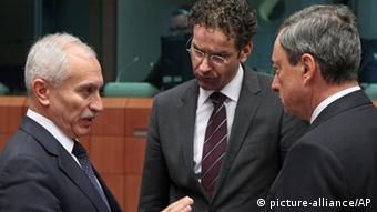 Cypriot Finance Minister Vassos Chiarly, left, talks with chairman of the Eurogroup and Dutch Finance Minister Jeroen Dijsselbloem, center, and President of the European Central Bank Mario Draghi, during the Eurogroup meeting, at the European Council building in Brussels, Monday, Feb. 11, 2013. Finance ministers from the 17 euro countries gathering in Brussels Monday have another important item on their agenda on top of the usual run-down of problems facing the region. As well as sitting down to discuss high unemployment, Cyprus's protracted bailout negotiations and the threat of a currency war hitting the euro, there is also the matter of a farewell dinner for Jean-Claude Juncker, who is stepping down from leading the Eurogroup. (AP Photo/Yves Logghe)