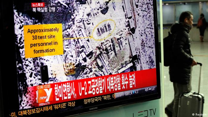 A passenger walks past a television report on North Korea's nuclear test at a railway station in Seoul February 12, 2013. North Korea conducted a nuclear test on Tuesday, South Korea's defence ministry said, after seismic activity measuring 4.9 magnitude was registered by the U.S. Geological Survey. The epicentre of the seismic activity, which was only one km below the Earth's surface, was close to the North's known nuclear test site. REUTERS/Kim Hong-Ji (SOUTH KOREA - Tags: POLITICS)