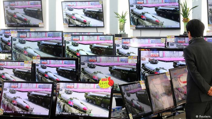 A customer look at television sets showing a report on North Korea's nuclear test at an electronics shop in Seoul February 12, 2013. North Korea conducted a nuclear test on Tuesday, South Korea's defence ministry said, after seismic activity measuring 4.9 magnitude was registered by the U.S. Geological Survey. REUTERS/Choi Jae-gu/Yonhap (SOUTH KOREA) NO SALES. NO ARCHIVES. FOR EDITORIAL USE ONLY. NOT FOR SALE FOR MARKETING OR ADVERTISING CAMPAIGNS. THIS IMAGE HAS BEEN SUPPLIED BY A THIRD PARTY. IT IS DISTRIBUTED, EXACTLY AS RECEIVED BY REUTERS, AS A SERVICE TO CLIENTS. SOUTH KOREA OUT. NO COMMERCIAL OR EDITORIAL SALES IN SOUTH KOREA