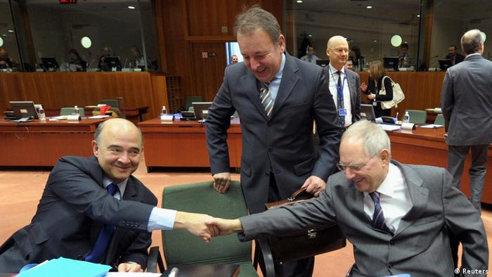 Spain's Economy Minister Luis de Guindos and Netherlands' Finance Minister Jeroen Dijsselbloem (R) shake hands, as Luxembourg's Finance Minister Luc Frieden looks on, during an euro zone finance ministers meeting at the European Union Council in Brussels February 12, 2013.