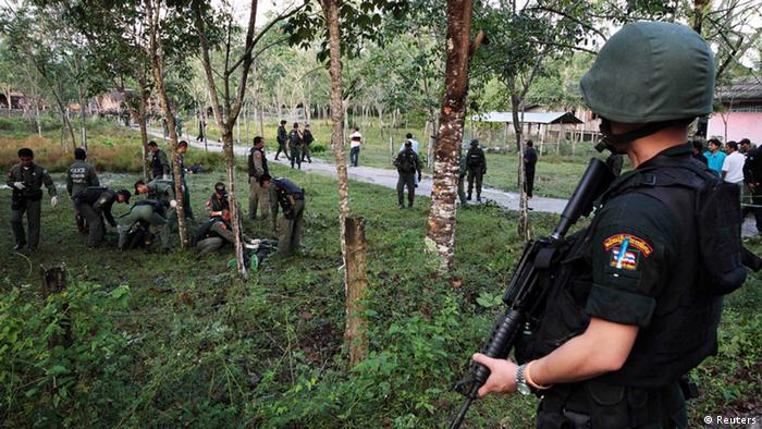 Security personnel investigate around bodies of insurgents at the site of an attack on an army base in the troubled southern province of Narathiwat February 13, 2013. Thai soldiers killed at least 17 Muslim insurgents who attacked a military base in a pre-dawn raid in the country's turbulent south, authorities said on Wednesday, the deadliest violence since the long-simmering conflict flared nine years ago. The gun battle between soldiers and about 60 insurgents in Narathiwat on the Malaysian border is the latest in a series of attacks pushing Thailand's three southernmost provinces to a crisis point after years of bloodshed. REUTERS/Surapan Boonthanom (THAILAND - Tags: RELIGION CIVIL UNREST MILITARY)