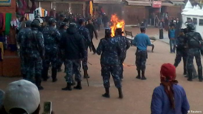 Nepalese police personnel and locals surround a Tibetan monk who set himself on fire at the premises of Boudhanath Stupa in Kathmandu