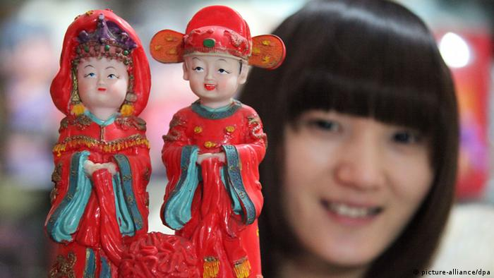 A saleswoman shows a clay sculpture in the shape of a married couple in Bozhou city, east Chinas Anhui province, 8 February 2012. Many businesses are busy preparing for the upcoming Valentines Day, which falls on Feb 14, hoping to take advantage of the great opportunity to make more money.