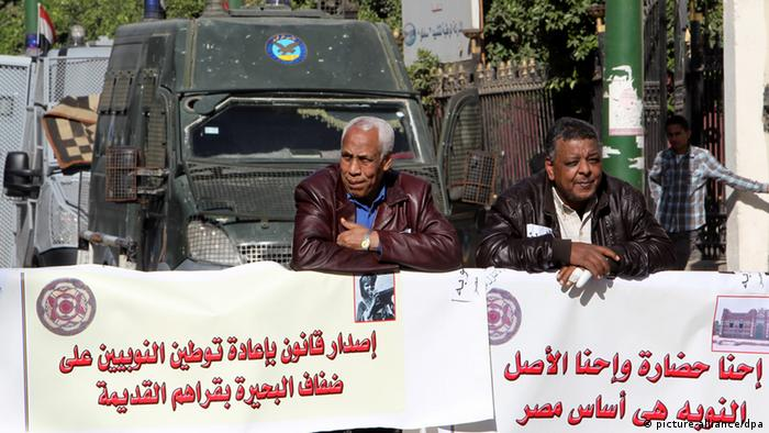 Egyptian Nubians stand next to banners written in Arabic demanding more rights (L) and stating that 'Nubian culture and civilization are the basis of Egypt' (R) as they take part in a protest in front of the Shura Council (lower house of the Parliament), in Cairo, Egypt, 19 January 2013. Egyptian Nubians took part in a gathering on 19 January in front of the Shura Council to demand more recognition to their culture language and history, a better representation as well as the right to return to areas in southern Egypt, where many communities had been moved to leave space for big development projects