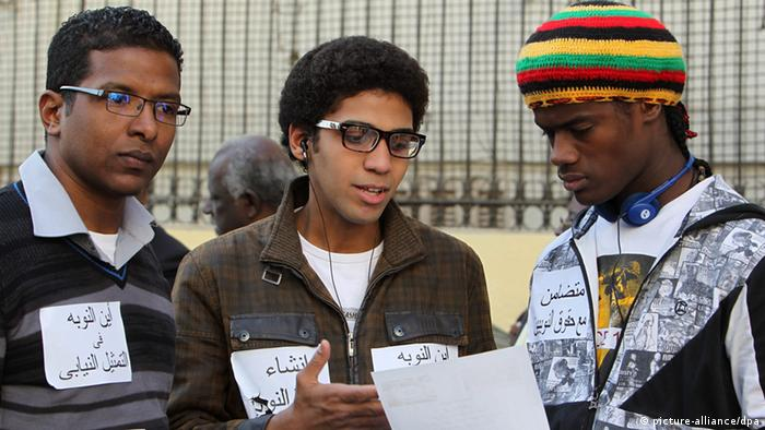 Young Egyptian Nubians, wearing stickers with messages demanding more rights for the Nubian people, read a fllyer at a protest in front of the Shura Council (lower house of the Parliament), in Cairo, Egypt, 19 January 2013. Egyptian Nubians took part in a gathering on 19 January in front of the Shura Council to demand more recognition to their culture language and history, a better representation as well as the right to return to areas in southern Egypt, where many communities had been moved to leave space for big development projects.