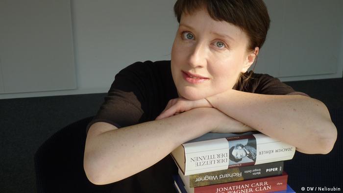 Anastassia Boutsko stützt sich mit den armen auf einen Stapel mit Wagner-Büchern (Foto: DW / Maksim Nelioubin)