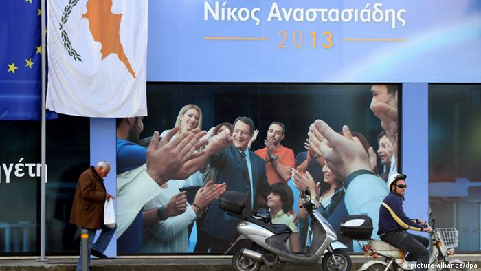 People walk past a giant poster of presidential candidate Nicos Anastassiades in Nicosia, Cyprus, on 07 February 2013.