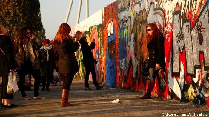 Young tourists take pictures in front of a piece of the Berlin wall. (Photo: Wolfram Steinberg)