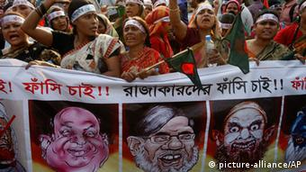 Bangladeshi women shout slogans demanding the execution of Jamaat-e-Islami leader Abdul Quader Mollah and others convicted of war crimes involving the nation's independence war in 1971, in Dhaka, Bangladesh, Banner reads we demand the execution of those convicted of war crimes. (AP Photo/Pavel Rahman)