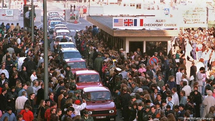 A long row of East German Trabant cars passing through Checkpoint Charlie into West Berlin is greeted by enthusiastic West Berliners, 10th November 1989.