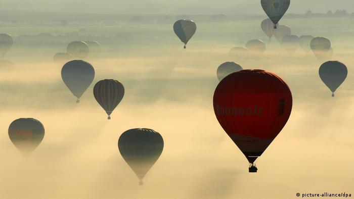 In Nebel und Sonnenlicht schweben viele Heißluftballons in der Luft