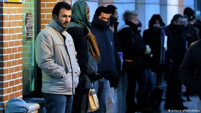 People line up next to a brick building (Photo: EPA/FERNANDO VILLAR)