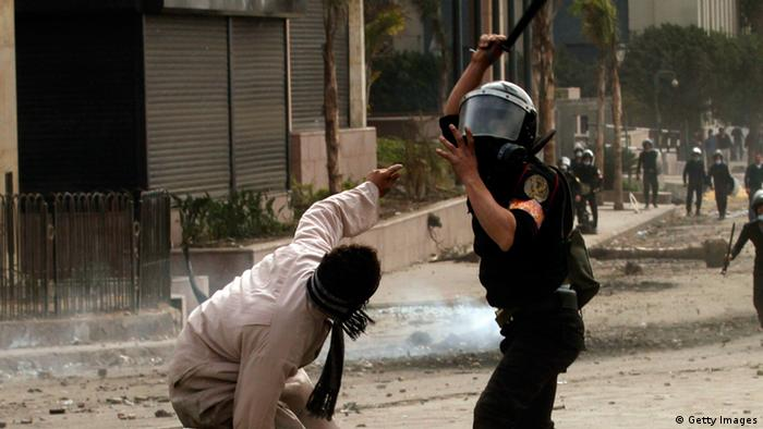A policeman in black hits a civilian wearing a facemask (Photo: MOHAMMED ABED/AFP/Getty Images)