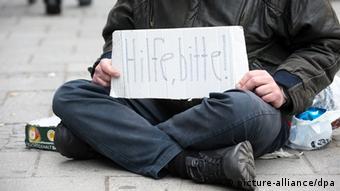 Ein Bettler sitzt auf einem Gehsteig in München (Oberbayern) und hält ein Schild mit der Aufschrift Hilfe, bitte! in Händen. (Foto: dpa)