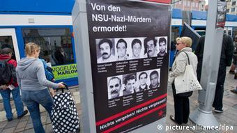 Passanten vor dem Rostocker Rathaus schauen sich ein ein Plakat mit Fotots der NSU-Opfer an. ( Foto: Stefan Sauer dpa/lmv)