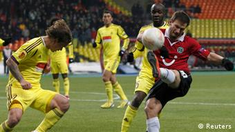 Anzhi Makhachkala's Andrei Eschenko (L) fights for the ball with Hanover's Szabolcs Huszti