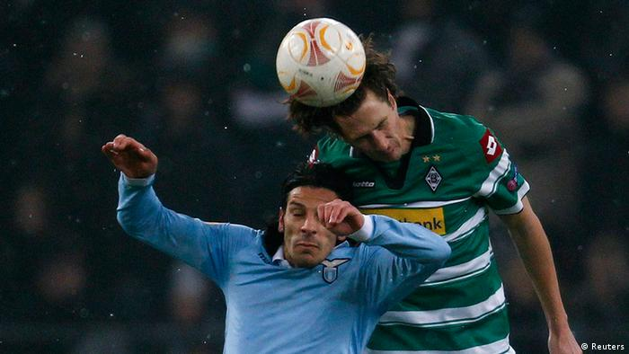 Lazio's Sergio Floccari and Borussia Moenchengladbach's Roel Brouwers (R) head a ball during their Europa League soccer match in Moenchengladbach February 14, 2013. REUTERS/Ina Fassbender (GERMANY - Tags: SPORT SOCCER)