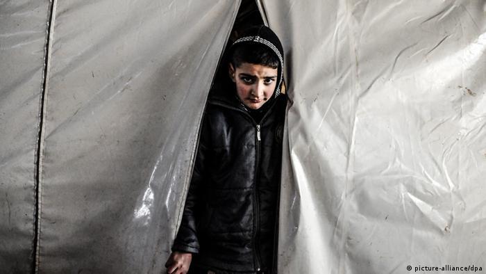 Ein syrischer Flüchtling guckt aus einem Zelt (Foto: James Keogh/Wostok Press/Maxppp)