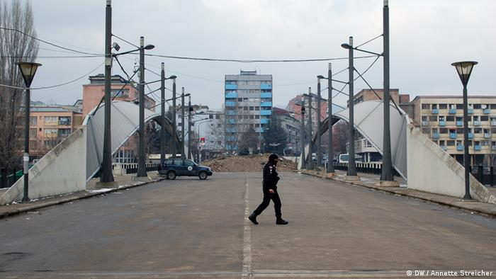 A man walks across the street in front of barricades on a bridge. (Photo: Anette Streicher/ DW)