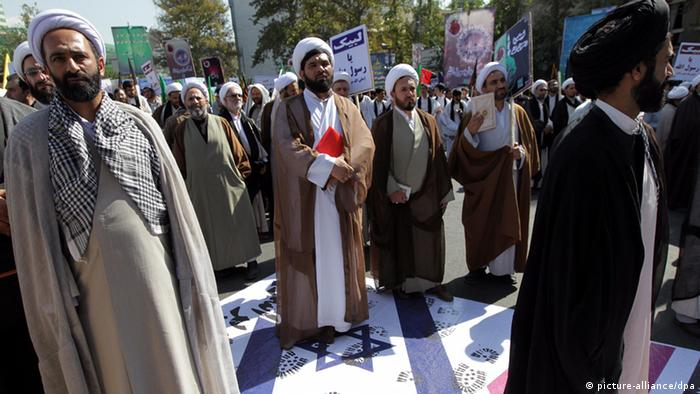 Iranian clergymen in traditional clothing stand on a poster with an Israeli flag on it during an anti-Israel rally in Tehran in 2012. (Photo:EPA/ Abedin Taherkenareh)
