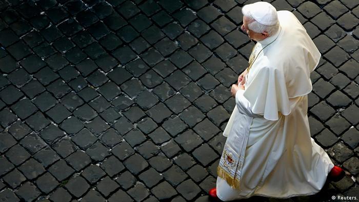 Papst Benedikt XVI. geht über einen gepflasterten Platz.