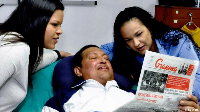 Venezuela's President Hugo Chavez holds a copy of the newspapers as his daughters, Rosa Virginia (R) and Maria watch while recovering from cancer surgery in Havana in this photograph released by the Ministry of Information on February 15, 2013. Venezuela's government published the first pictures of cancer-stricken Chavez since his operation in Cuba more than two months ago, showing him smiling while lying in bed reading a newspaper, flanked by his two daughters. The 58-year-old socialist leader had not been seen in public since the Dec. 11 surgery, his fourth operation in less than 18 months. The government said the photos were taken in Havana on February 14, 2013. REUTERS/Ministry of Information/Handout (VENEZUELA - Tags: POLITICS PROFILE HEALTH) ATTENTION EDITORS - THIS IMAGE WAS PROVIDED BY A THIRD PARTY. FOR EDITORIAL USE ONLY. NOT FOR SALE FOR MARKETING OR ADVERTISING CAMPAIGNS. THIS PICTURE IS DISTRIBUTED EXACTLY AS RECEIVED BY REUTERS, AS A SERVICE TO CLIENTS