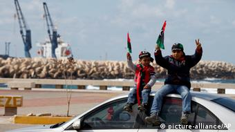 Libyan children wave national flags near the seaport during a rally in Benghazi, Libya, Friday, Feb, 15, 2013. Libyans are preparing to mark the second anniversary of the uprising that ousted Moammar Gadhafi. (AP Photo/Mohammad Hannon)