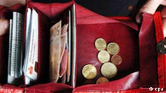An open wallet with coins and bank notes inside