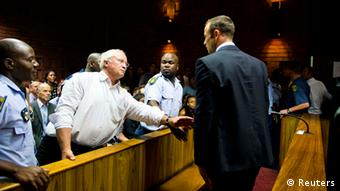 South African Blade Runner Oscar Pistorius (R) talks to his father Henke after his court appearance in Pretoria February 15, 2013. Pistorius, a double amputee who became one of the biggest names in world athletics, broke down in tears on Friday after he was charged in court with shooting dead his girlfriend, 30-year-old model Reeva Steenkamp, in his Pretoria house. REUTERS/Stringer (SOUTH AFRICA - Tags: SPORT ATHLETICS CRIME LAW) NO SALES. NO ARCHIVES. FOR EDITORIAL USE ONLY. NOT FOR SALE FOR MARKETING OR ADVERTISING CAMPAIGNS. THIS IMAGE HAS BEEN SUPPLIED BY A THIRD PARTY. IT IS DISTRIBUTED, EXACTLY AS RECEIVED BY REUTERS, AS A SERVICE TO CLIENTS. SOUTH AFRICA OUT. NO COMMERCIAL OR EDITORIAL SALES IN SOUTH AFRICA