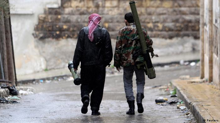 Members of the Free Syrian Army walk with their weapons in Al Izaa district in Aleppo February 16, 2013. REUTERS/Muzaffar Salman (SYRIA - Tags: CONFLICT POLITICS CIVIL UNREST)