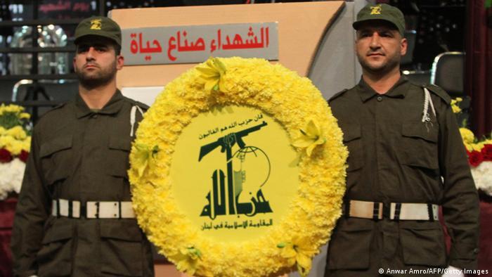 Mitglieder der militanten Schiiten-Organisation Hisbollah tragen ihr Wappen - Foto: Anwar Amro (AFP)