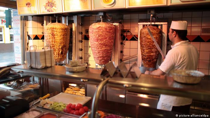 A Turkish kebab shop in Cologne: an employee is slicing cuts off a slab of meat. (Photo: Oliver Berg dpa/lnw)