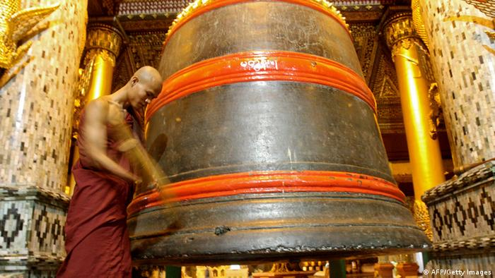 Ein buddhistischer Mönch läutet eine Bronzeglocke in der Shwedagon-Pagode in Yangon - Foto: AFP/AFP/Getty Images