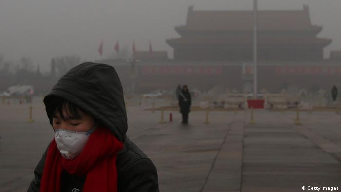 BEIJING, CHINA - JANUARY 31: A tourist wearing the masks walks on the Tiananmen Square during severe pollution on January 31, 2013 in Beijing, China. Heavy smog that has choked Beijing for the last five days weakened slightly on Thursday due to a light rainfall, although the capital's air remains heavily polluted. The haze choking many Chinese cities covers a total area of 1.43 million square kilometers, the China's Ministry of Environmental Protection said Wednesday. (Photo by Feng Li/Getty Images)