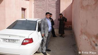 A man stands next to his white car, surrounded by the walls of a pink building (Photo: Rechte liegen bei Abbas Ali Bakhshi und Fritz Maya)