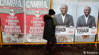 A woman walks past electoral posters in Rome (Photo: REUTERS/Tony Gentile)