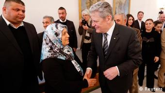 German President Joachim Gauck (R) welcomes Ayse Yozgat during a meeting of relatives of the victims who were killed by the small neo-Nazi group National Socialist Underground (NSU) at the Presidential residence Bellevue castle in Berlin February 18, 2013. The neo-Nazi group NSU is accused of murdering nine Turkish and Greek immigrants and a policewoman from 2000 to 2007. REUTERS/Fabrizio Bensch (GERMANY - Tags: CRIME LAW POLITICS)