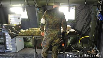 A German soldier stands beside another soldier lying on a medical stretcher inside a military tent (c) dpa - Bildfunk+++