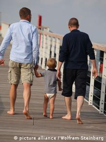 Two men walk with a little boy on the beach (Photo: Wolfram Steinberg)