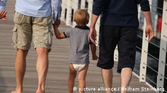 Zwei Männer gehen mit einem kleinen Jungen an der Hand über einen Steg an der Ostsee in Timmendorfer Strand im Juli 2012. Foto: Wolfram Steinberg