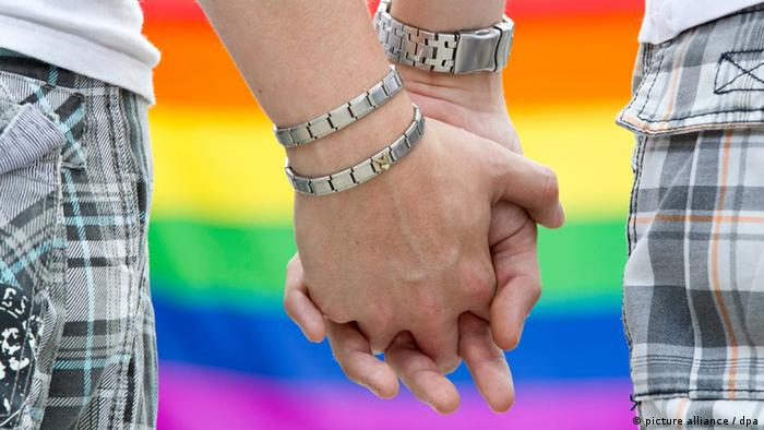 Two males holding hands in front of a rainbow flag