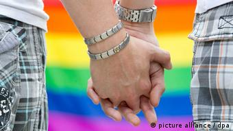 Two hands clasp each other in front of a rainbow-colored flag, Photo: Michael Reichel
