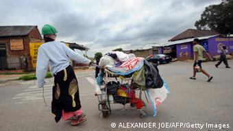 A woman collecting plastic bags carries her cart through the streets of Johannesburg's Alexandra township. ALEXANDER JOE/AFP/Getty Images)