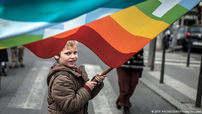 A person holds a placard reading Equality for all children .... as a boy waves a rainbow flag during a demonstration to support gay marriage and adoption on January 26, 2013 in Lyon, central France. French government plans to put the proposed legislation to parliament on January 29. AFP PHOTO / JEFF PACHOUD (Photo credit should read JEFF PACHOUD/AFP/Getty Images)