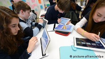 Kinder sitzen an einem Tisch und spielen auf Tablets und Laptops