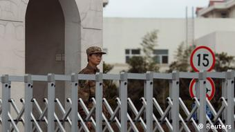 A Chinese People's Liberation Army soldier stands guard in front of 'Unit 61398', a secretive Chinese military unit, in the outskirts of Shanghai, February 19, 2013.