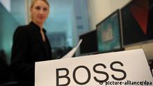 ILLUSTRATION - Eine Frau sitzt am 03.01.2013 an einem Schreibtisch vor einem Computer in einem Büro in Berlin und ließt einen Vertrag. Vor ihr steht ein Schild mit der Aufschrift Boss. Foto: Jan-Philipp Strobel/dpa pixel