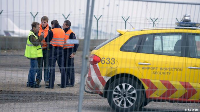Airport security guards and officials stand near an entrance to the tarmac at Zaventem international airport near Brussels February 19, 2013. Robbers dressed as police and armed with machineguns have stolen 120 parcels of diamonds worth millions of dollars from the runway of Brussels Airport in one of the biggest heists the industry has seen. REUTERS/Eric Vidal (BELGIUM - Tags: TRANSPORT CRIME LAW BUSINESS)