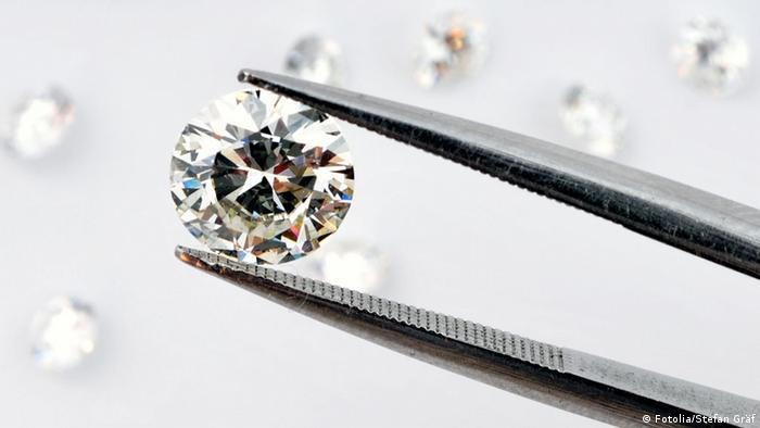 A close-up photo of a diamond, held in special tweezers for inspection
