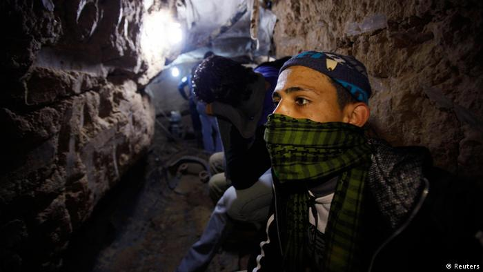 A Palestinian works inside a smuggling tunnel flooded by Egyptian forces, beneath the Egyptian-Gaza border in Rafah, in the southern Gaza Strip February 19, 2013. Egypt will not tolerate a two-way flow of smuggled arms with the Gaza Strip that is destabilising its Sinai peninsula, a senior aide to its Islamist president said, explaining why Egyptian forces flooded sub-border tunnels last week. To match Interview PALESTINIANS-TUNNELS/EGYPT REUTERS/Ibraheem Abu Mustafa (GAZA - Tags: POLITICS CIVIL UNREST)